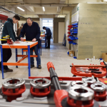 Student learning plumbing skills in workshop
