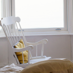 white rocking chair in front of bay window