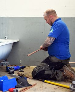 Mental Health In The Trades - Plumbing student installing a bath
