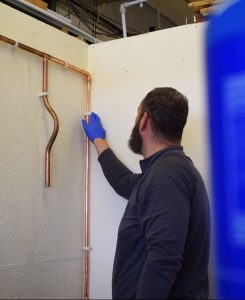 Mental Health In The Trades - Plumbing student working on copper pipes