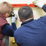 Investing New Career - Two students in the gas workshop measuring using a level