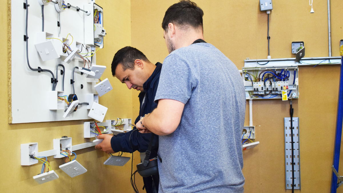 Mentor - Two electrical trainees working on wiring in workshop bay