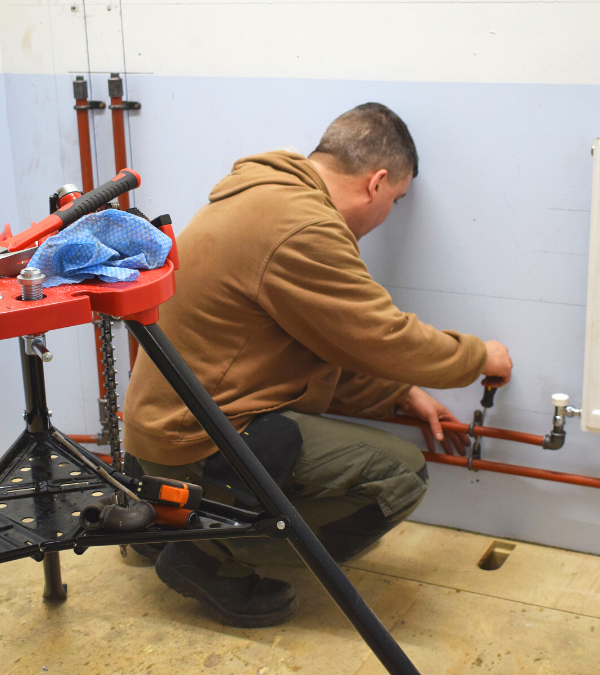 Plumbing trainee working on radiator pipe work - What Are The Trades