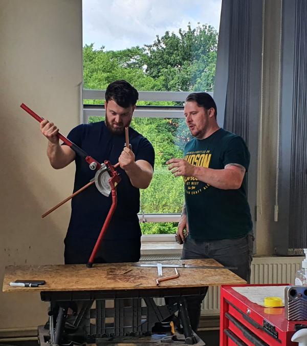 Two gas engineers working on pipe bending - Public Response To Going Green