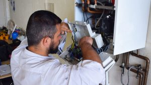 Gas engineer trainee working on a boiler - Going Green