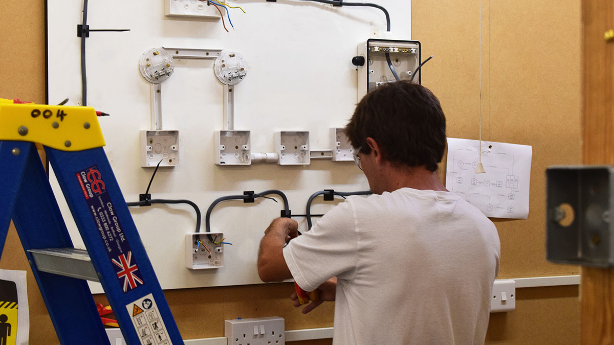 Electrical training course student working at electrical board